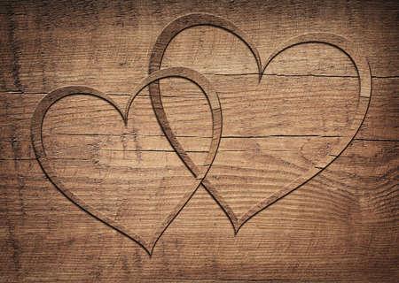 puertas de madera: Dos corazones de madera colocados en una tabla de madera de color marrón.
