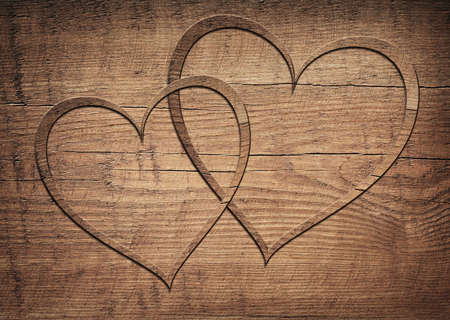 wooden planks: Two wooden hearts placed on a brown wood board.