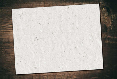 paper board: Gray recycled paper is on grunge wooden board.