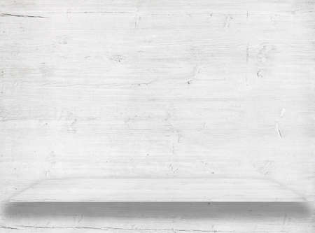 White wood wall with wooden shelf or table surface.
