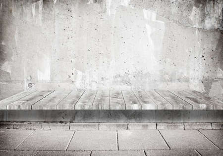 table surface: Concrete grunge weathered gray wall with wooden shelf, table surface and tile walkway.