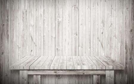 Leeg grijze tafel naast houten muur.