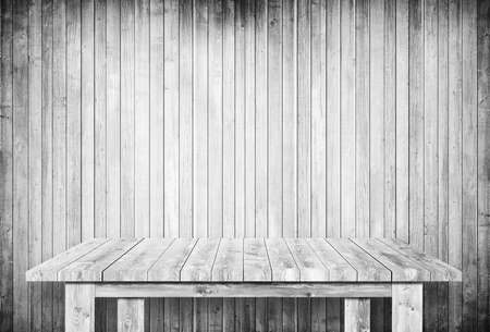 Empty gray table next to wooden wall.