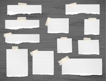 tabletop: Pieces of ripped white note paper are stuck on dark wooden wall or tabletop.