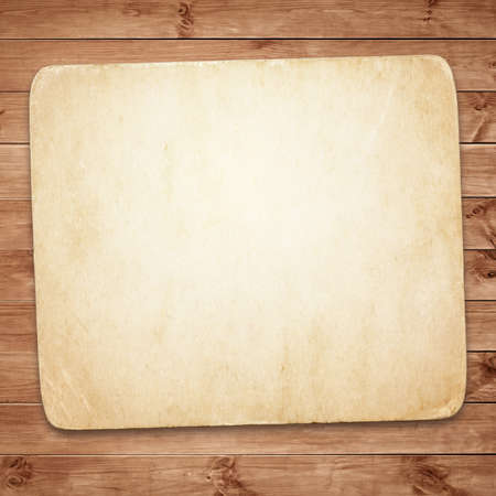 suface: Old dirty paper with shadow on brown wooden wall or tabletop suface. Stock Photo