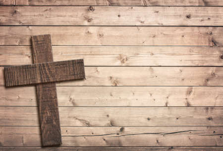 cristianismo: Cruz de madera en tablero de la mesa de edad marrón o superficie de la pared. Foto de archivo