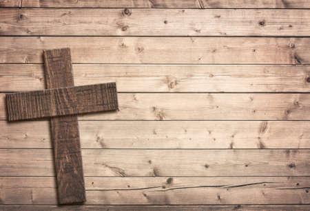 Holzkreuz auf braunem alten Tisch- oder Wandfläche. Standard-Bild