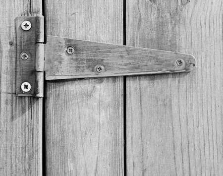 rusty nail: Close up of screwed hinge on wooden door.