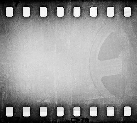 Grunge gray scratched dirty film strip with movie reel background.