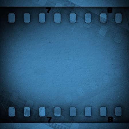 Dark grunge scratched dirty film strip. Blue background. Banco de Imagens