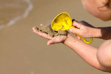 Hands of a child close-up. A child plays with sand and a shovel on the beach. Rest on the seashore. Imagens