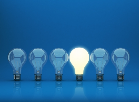 Fila de 3D bombilla de luz sobre fondo azul. Innovación concepto. Foto de archivo