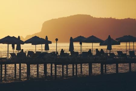 Silhouette of chairs and umbrellas on deck. Summer  resort of Alanya, Turkey Standard-Bild