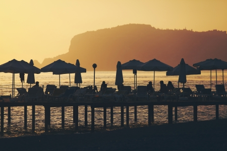 Silhouette of chairs and umbrellas on deck. Summer  resort of Alanya, Turkey Archivio Fotografico