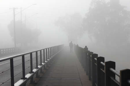 aloneness: Strolling Through the Mists of Bridge Over the Condamine River Stock Photo