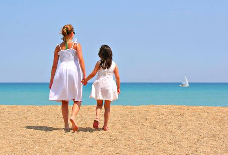 Two girls holding hands walking by the beach photo