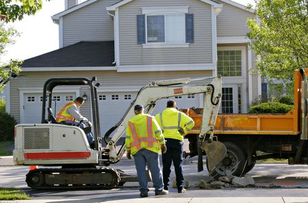 noise pollution: Construction worker working on residential street Stock Photo