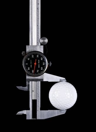 a caliper measuring a golf ball on black background
