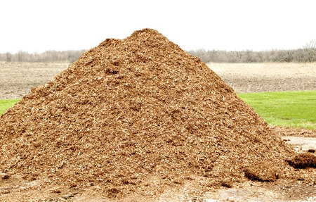 a pile of natural mulch on farm land