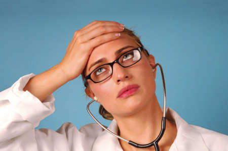 stressful: headache young female doctor stressful expression Stock Photo