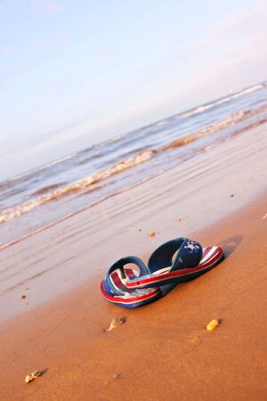 pair of sandles on beach in morning sun shine photo