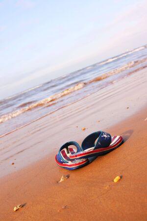 pair of sandles on beach in morning sun shine photo