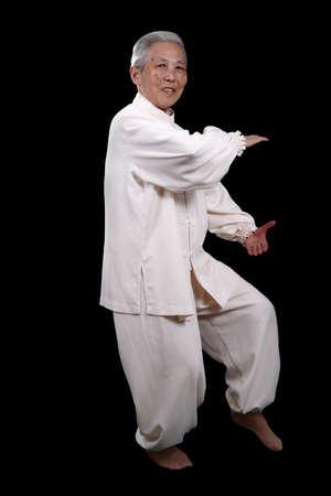 Chinese Elderly performing Tai Chi Isolated photo