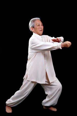 Chinese Elderly performing Tai Chi Isolated on Black Background Stock Photo - 2635177