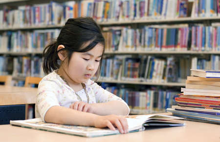 school library: Cute Little Girl Reading Books at Library Corner Stock Photo