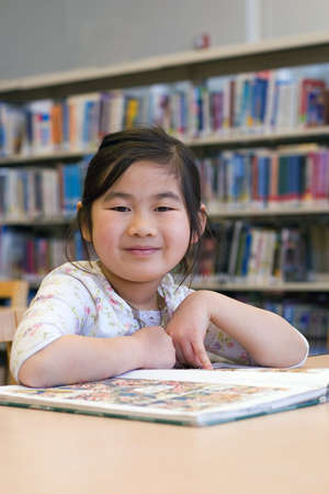 Cute Little Girl Reading Books at Library Corner photo