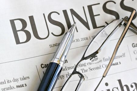 Pen and Eyeglasses on Business Newspaper Stock Photo