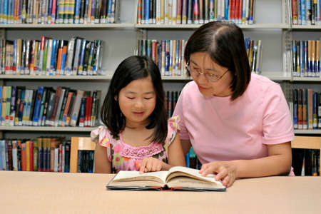 Mother and daughter reading book together at library