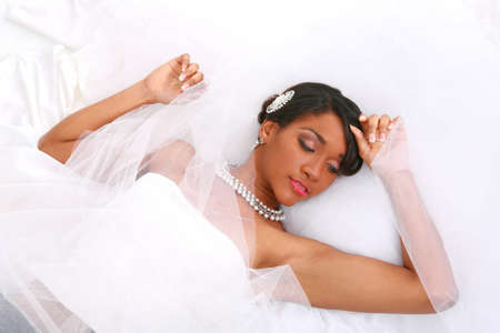 Beautiful Young Bride Laying Down Posing with Eyes Closed Smiling photo