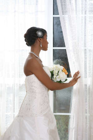 Beautiful Young Bride Looking Out Window In a Rainy Day With Bridal Rose Bouquet photo