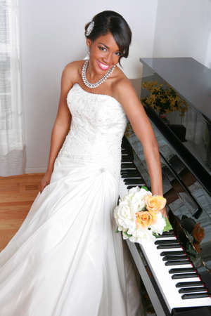 Beautiful Young Bride Standing by Piano With Bridal Rose Bouquet  photo
