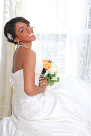 Beautiful Young Bride Sitting by Window With Bridal Rose Bouquet  photo