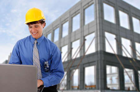 Construction Worker Checking Laptop in front of a Commercial Construction Building photo