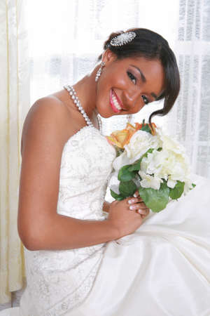 Beautiful Young Bride Sitting by the Window With Bridal Rose Bouquet