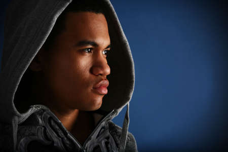 man profile: Young African American Male Low Key Portrait on Blue Background