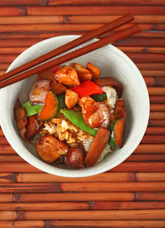 Bowl of Stewed Chicken and Vegetables over White Rice on Bamboo Placemat Stock Photo