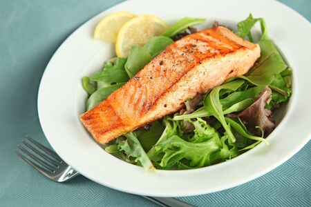 Grilled Salmon Fellet over Green Salad Plate Stock Photo