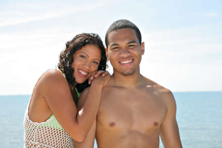 Young Couple Smiling by Water Front under Summer Blue Skey photo