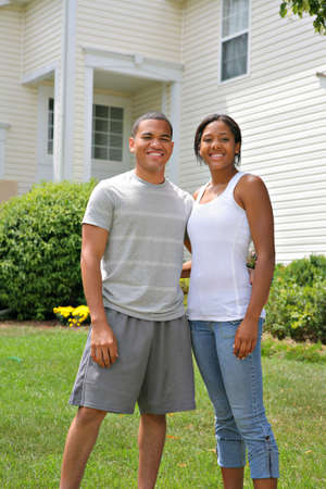 Two Happy smiling African American Home Owners in front of House photo