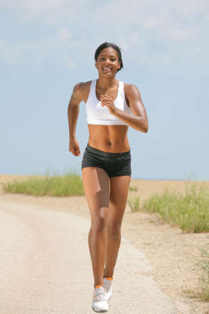 Healthy Natural Looking Young African American Female Runner under Summer Sunlight photo