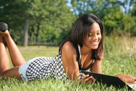 Young African American Female Reading Book Outdoor in Summer photo