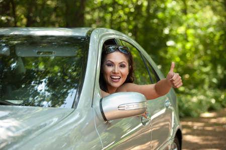 Joyful Asian Female Driver Arm Out of Car Window photo