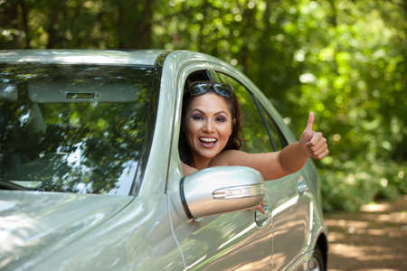Joyful Asian Female Driver Arm Out of Car Window photo