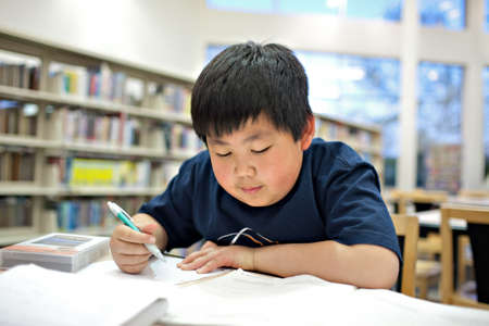 Asian School Boy Working on Homework at Library, Shallow DOF photo
