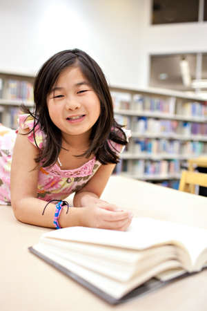 Smiling School Girl Reading Book at Library, Shallow DOF photo