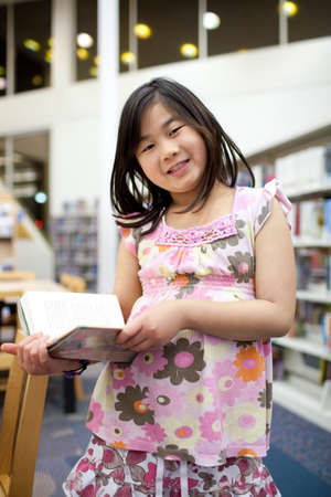 Smiling Asian School Girl Reading Book at Library, Shallow DOF photo